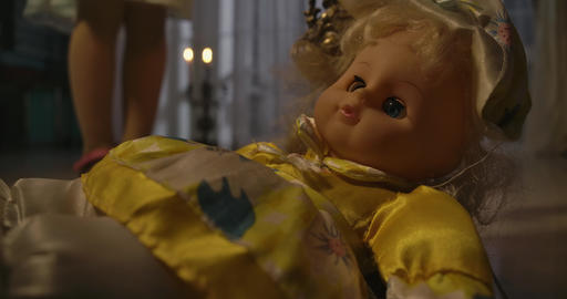 Close-up of strange doll lying on floor in candlelight. Little Caucasian girl's Live Action