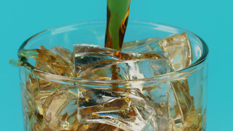 Pouring cola soft drink into a glass with ice cubes on cyan background, slow Live Action