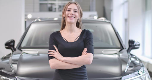 Portrait of smiling Caucasian girl posing in front of new black automobile Live Action