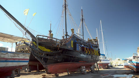 A pirate ship is under restoration. An old black ship stands on land Live Action