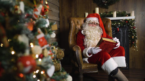 Santa Claus pulling out old red silk album near christmas tree with toys and Live Action