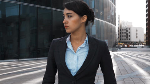 Serious businesswoman walk outdoor and look at camera Live Action