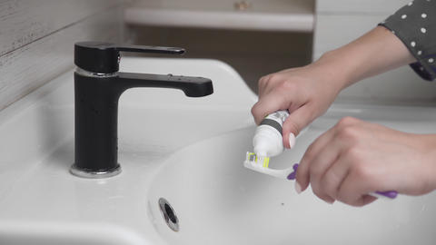 Young woman brushing teeth with a tooth brush in bathroom. Close-up of hands Live Action