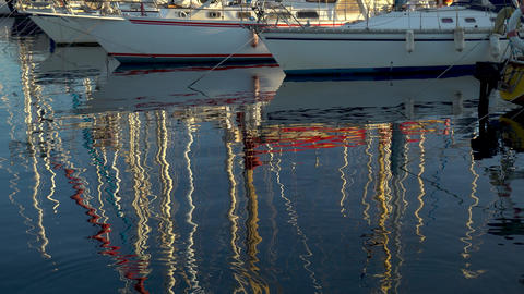 Masts of ships are reflected in the water. Modern ships are in the bay. Panorama Live Action