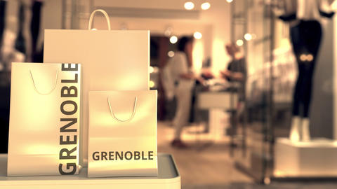 Paper shopping bags with Grenoble caption against blurred store entrance. Retail Live Action