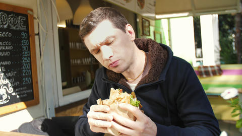 Man eating a sandwich on the street Live Action