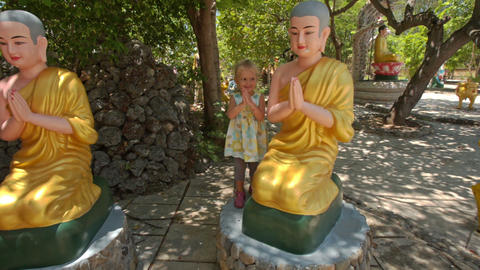 Little Girl Plays at Sitting Buddha Statues in Temple Park Footage