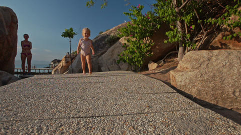 Little Girl Runs along Rocky Path on Beach from Mother Footage