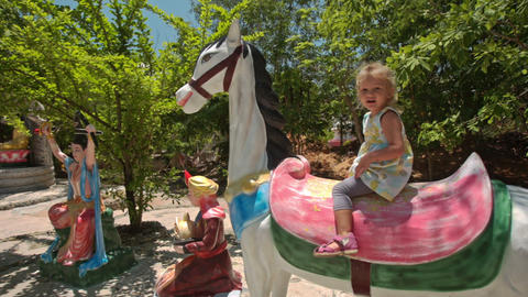 Little Girl Sits on Horse Model on Playground in Temple Park Footage