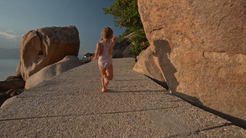 Backside Little Girl Runs along Rocky Path on Beach Footage