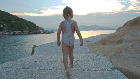 Little Girl Runs along Coast on Rocky Path at Sunset Footage