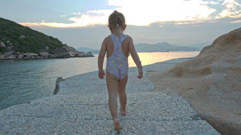 Little Girl Runs along Coast on Rocky Path at Sunset Footage