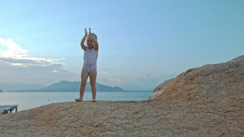 Little Girl Stands on Rock Top Claps Hands at Sunset on Beach Footage