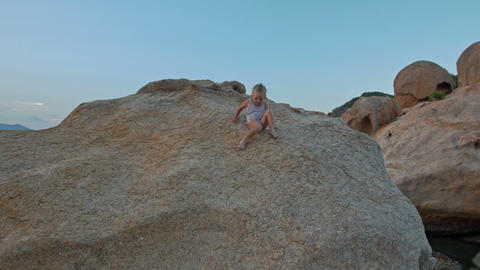 Little Girl Climbs Down Large Rock Top at Sunset on Beach Footage