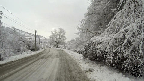 Empty road in the mountains during winter with snow covered trees on the side Footage
