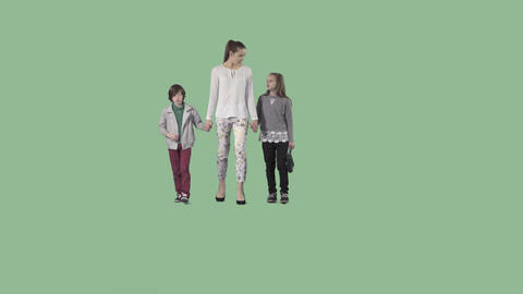 Young beautiful mother with two attractive children are walking at the camera Live Action
