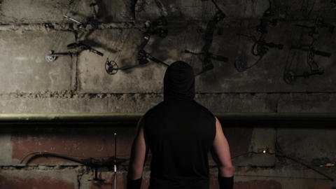 A man in black clothes looks at the wall with bows and crossbows Live Action