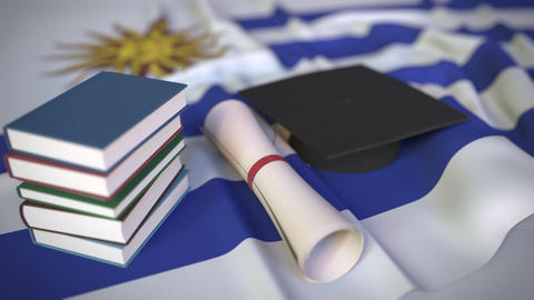 Graduation cap, books and diploma on the Uruguayan flag. Higher education in Live Action