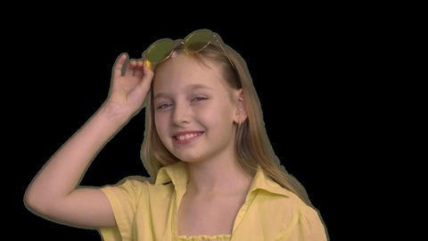 Portrait smiling girl on yellow dress wearing yellow glasses isolated on black Live Action