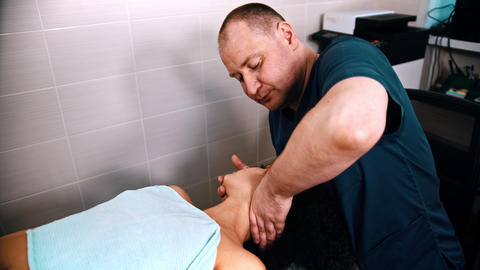 Chiropractic treatment - the doctor specialist giving a woman patient a neck Live Action