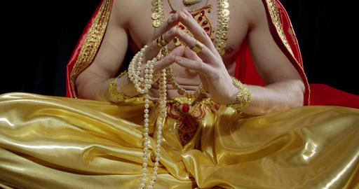 Close up of sitting in lotus position Surya the god of sun, wearing jewelry, 4k Live Action