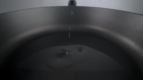 Sunflower oil drops fall to the hot pan in slow motion, greasing the pan Live Action