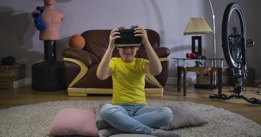Portrait of smiling Caucasian boy in casual clothes taking on VR headset. Cute Live Action