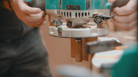 Carpentry indoors - a man woodworker taking off a polishing machine from the Live Action