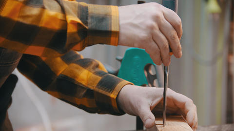 Carpentry - a man woodworker cutting out the recess on the wooden block Live Action