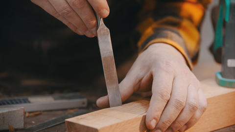 Carpentry - a man woodworker cutting out the recess on the wooden block with a Live Action