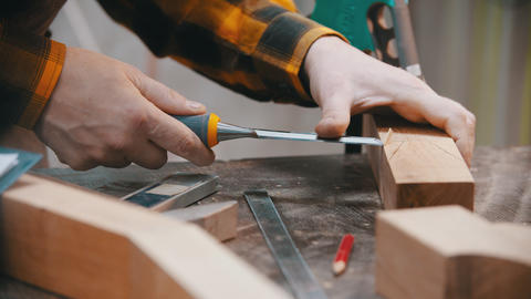 Carpentry - a woodworker cutting out the recess on the wooden block Live Action