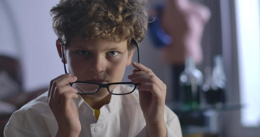 Close-up of cute Caucasian boy with curly hair taking off and putting on Live Action