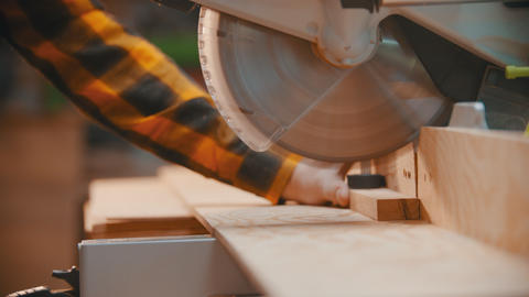 Carpentry - a woodworker cutting the wooden detail with a sharp circular saw - Live Action