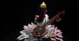 Saraswati in white dress is sitting on a big flower and holding veena, 4k Live Action