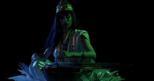 Indian deity Saraswati with beads in her hands is lying down on veena, 4k Live Action