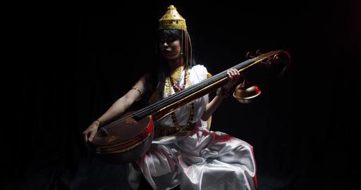 Low lighting, Saraswati is sitting and holding big musical instrument veena, 4k Live Action