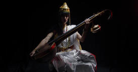 Saraswati the goddess of knowledge with veena in her hands, black background 4k Live Action