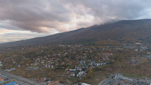 Aerial view of scenic colorful clouds above mountain near busy city bypass road Live Action