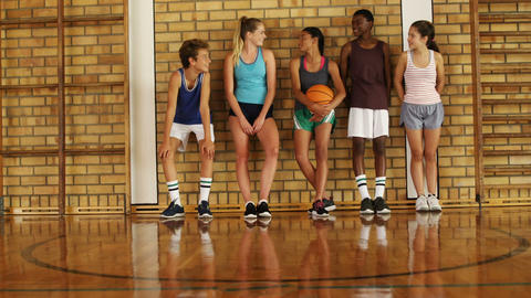 High school kids leaning against the wall in basketball court Live Action
