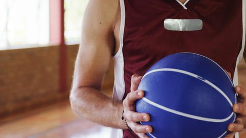Determined basketball player holding a basketball Live Action