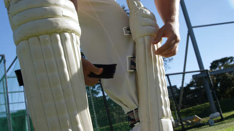 Cricket player tying his batting pads during a practice session Live Action