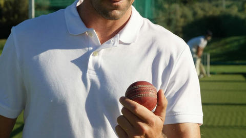 Confident cricket player holding ball during a practice session Live Action