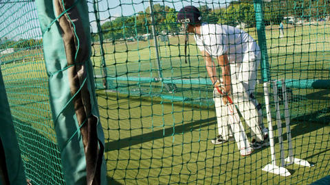 Cricket players practicing in the nets during a practice session Live Action