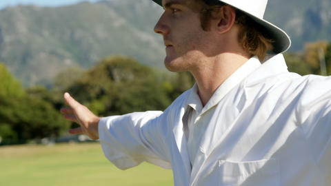 Cricket umpire signaling wide ball during match Live Action