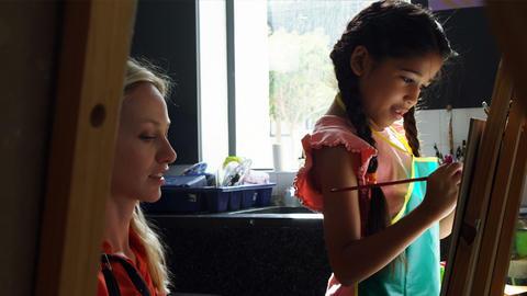 Teacher assisting schoolgirl in drawing class Live Action