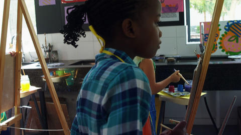 Attentive schoolkids panting on canvas Live Action