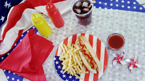Hot dog, french fries and cold drink served on a table with 4th july theme Live Action