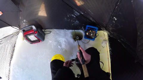 Man preparing for ice fishing in snowy region Live Action