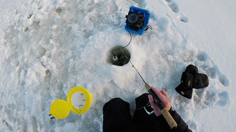 Ice fisherman fishing in snowy region Live Action
