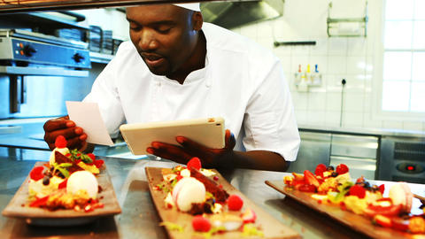 Chef looking at order list while using digital tablet at order station Live Action